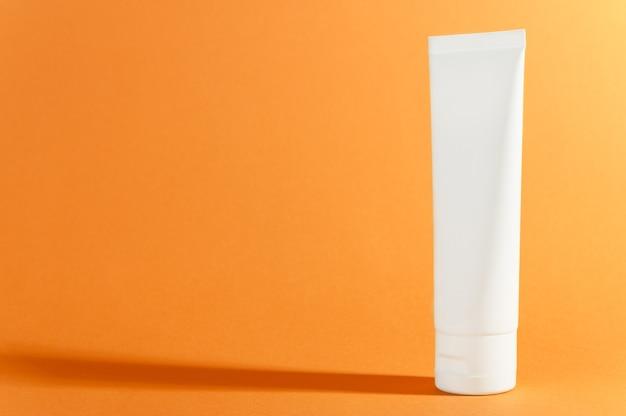 影のある明るい日当たりの良いオレンジ色のクリーム色のチューブ