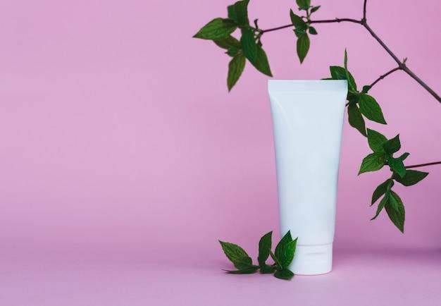 Крем-тюбик на розовом фоне косметический продукт по уходу за кожей пустой пластиковый пакет белый лосьон без марочного знака бальзам крем для рук зубная паста макет флакон солнцезащитного крема