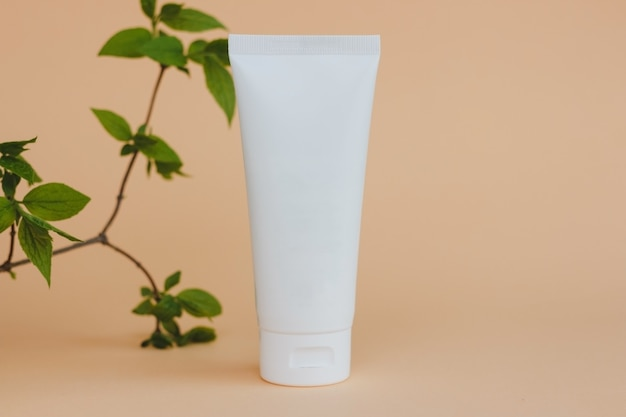 Cream in white tube with natural leaves