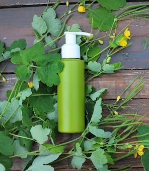 Крем с макетом травы чистотела, плоский вид сверху на деревянном фоне