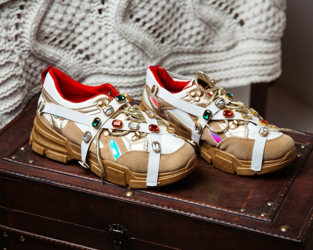 Cream woman sneakers with colourful stones on it and golden details