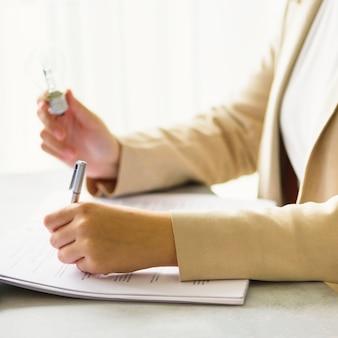 Рука женщины держа электрическую лампочку, тетрадь, компьтер-книжку, ручку, документы на cream предпосылке с космосом экземпляра. креативная идея, новый бизнес-план, мотивация, инновации, концепция вдохновения.