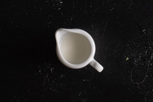 黒いテーブルの上にクリームとクリーマー。ミルクとミルクの水差し。