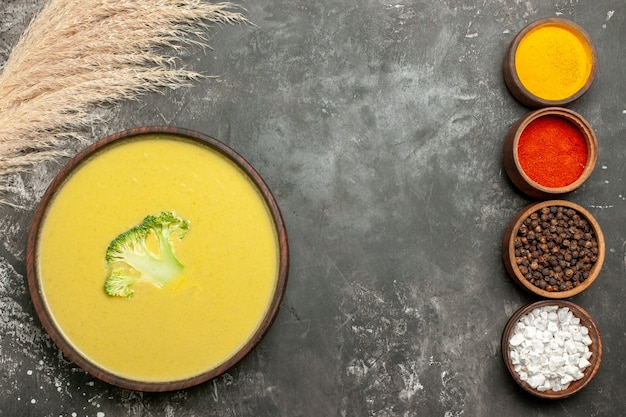 Creamy broccoli soup in a brown bowl and different spices on gray table