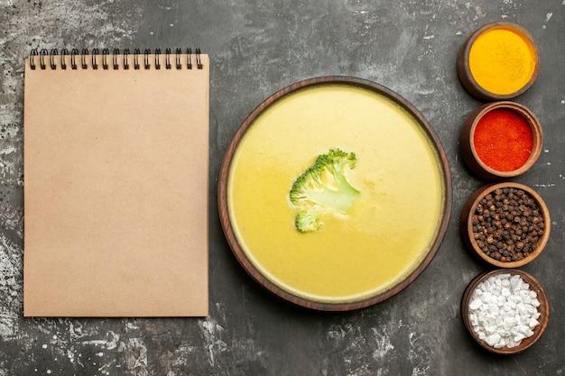 茶色のボウルにクリーミーなブロッコリースープと灰色のテーブルのノートの横にあるさまざまなスパイス