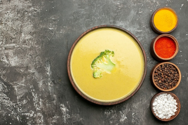 Сливочный суп из брокколи в коричневой миске и разные специи на левой стороне серого стола