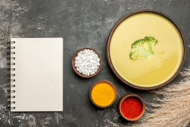 茶色のボウルにクリーミーなブロッコリースープと灰色のテーブルにノートブックとさまざまなスパイス