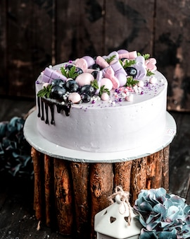 Creamy cake in lilac topped with pink lilac decorations and grapes