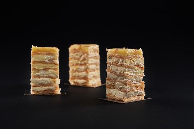 Сливочные кусочки торта, десерт из белого яблока, изолированные на черном.
