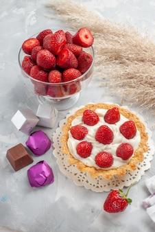 Сливочный торт со свежей красной клубникой и шоколадными конфетами торт на белом столе, торт фруктово-ягодный бисквитный крем сладкий