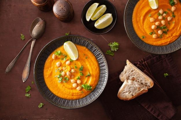 暗い素朴な背景にクリーミーなニンジンひよこ豆のスープ