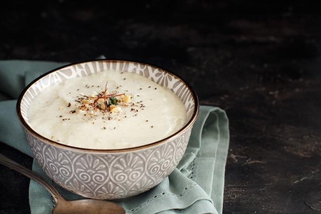 暗い背景のボウルにクリーミーなカリフラワースープ