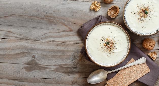 木製のテーブルトップビューでクリーミーなカリフラワーのスープ Premium写真