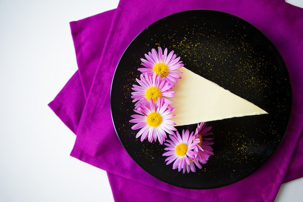 Creamy cheesecake decorated with purple flowers on a bright napkin
