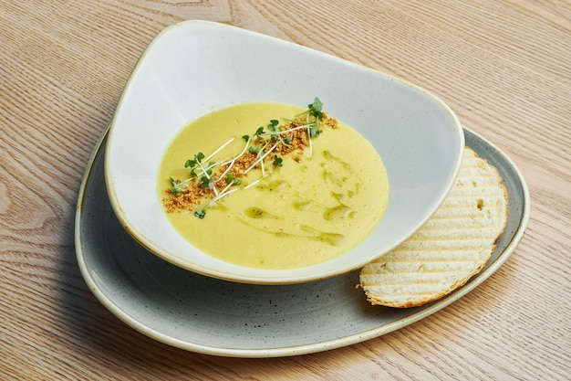 Creamy cream soup in a beautiful bowl with crackers, fried bread and microgreen. tasty food for lunch.