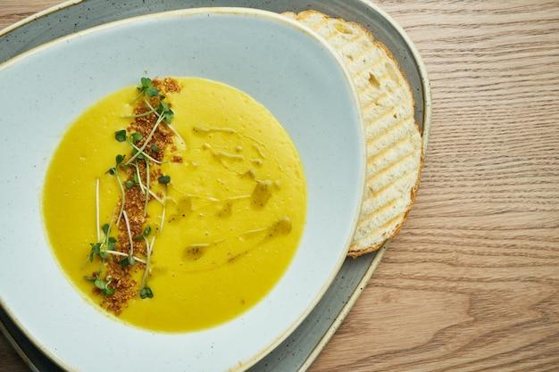 Сливочный крем-суп в красивой миске с крекерами, жареным хлебом и микрогрин. вкусная еда на обед. деревянный фон