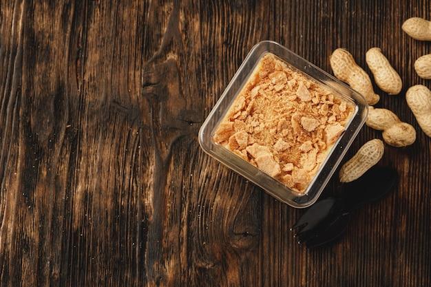 木製のテーブルの上のプラスチックの箱にクリーミーなデザートをクローズアップ