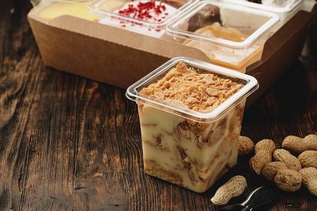 木製のテーブルの上のプラスチックの箱でクリーミーなデザート