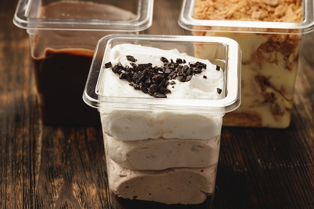 Creamy dessert in a plastic box on wooden table
