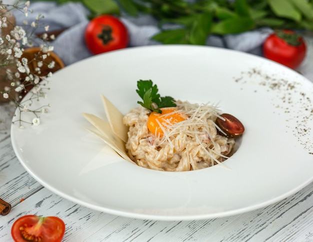 Creamy fusilli pasta garnished with parmesan slices, parsley and black cherry tomato