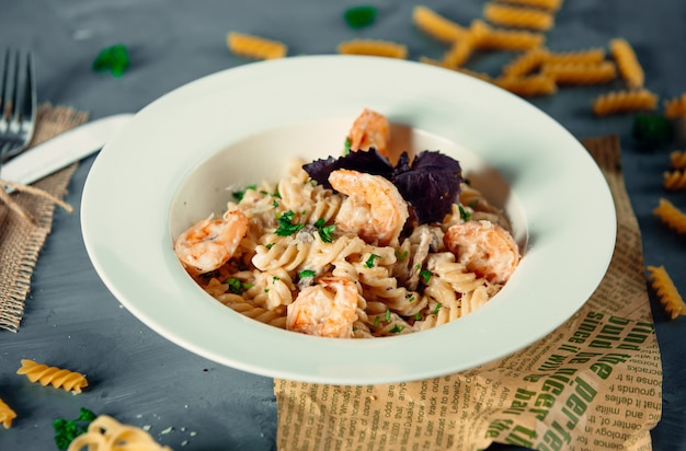 Creamy fusilli pasta with fried shrimps and fresh herbs