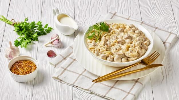 Сливочно-чесночный грибной соус, обжаренные в сметанном соусе шампиньоны, подаются в белой миске на деревянном столе, пейзажный вид сверху