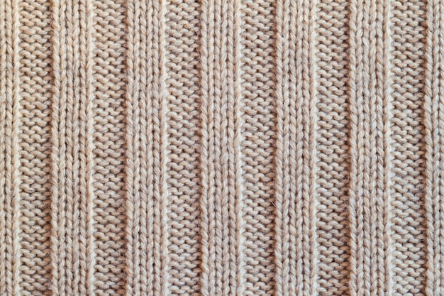 Creamy knitted wool warm clothes for the winter fabric texture background