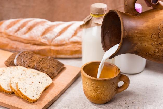 まな板の上の2つのガラス瓶とスライスされたパンの横にあるマグカップに装飾的な木製の水差しから注ぐクリーミーな牛乳