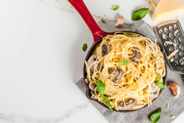 Creamy mushroom pasta with cheese and basil, in portioned frying pan, on white marble table top view