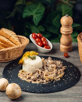 Creamy mushroom served with rice in a round stone plate