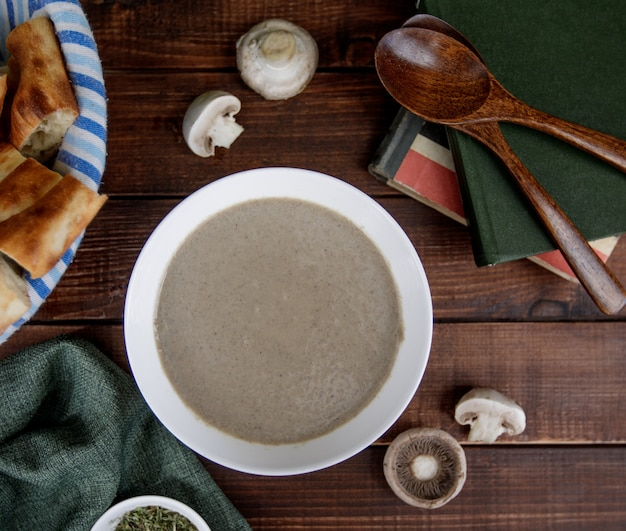 Creamy mushroom soup inside a white bowl served with bread, top vire