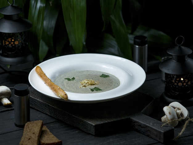 Creamy mushroom soup served with galette bread sticks