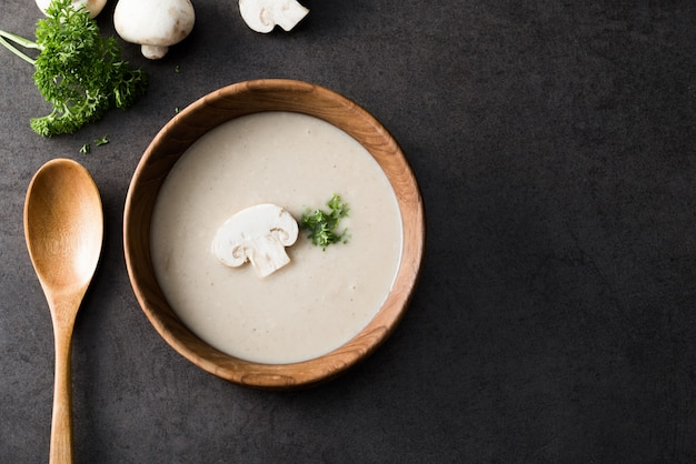Creamy mushroom soup on wood with champignons mushrooms