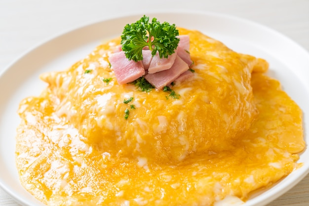 Creamy omelet with ham on rice
