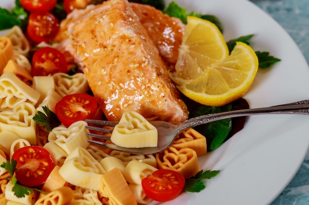 Creamy pasta in the form of a heart with salmon in white plate