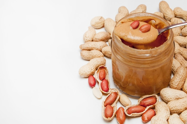 Creamy peanut butter in glass jar, peanut and spoon isolated on white background. a traditional product of american cuisine.