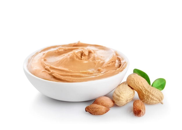 Creamy peanut butter in small bowl isolated on white