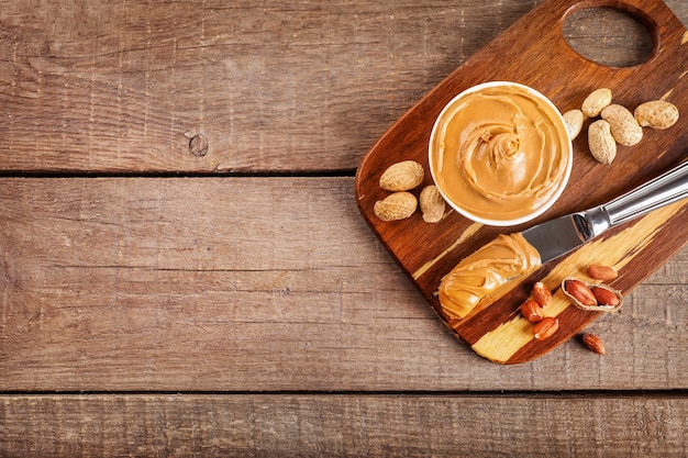 Creamy peanut butter in small bowl and knife with peanut butter on wooden cutting board on wooden