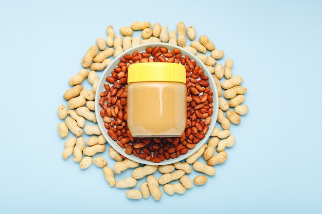 Creamy peanut paste in glass jar  peanuts in shell, peeled peanuts on color background