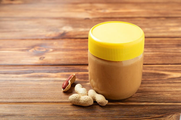 Creamy peanut paste in glass jar with yellow cap and peanuts in the peel scattered on brown wooden table
