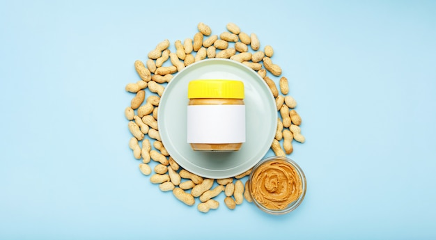 Creamy peanut paste in glass jar with yellow cap with mock up and peanut butter in a glass plate. peanuts in the peel scattered on blue background. minimalistic food flat lay on color background.