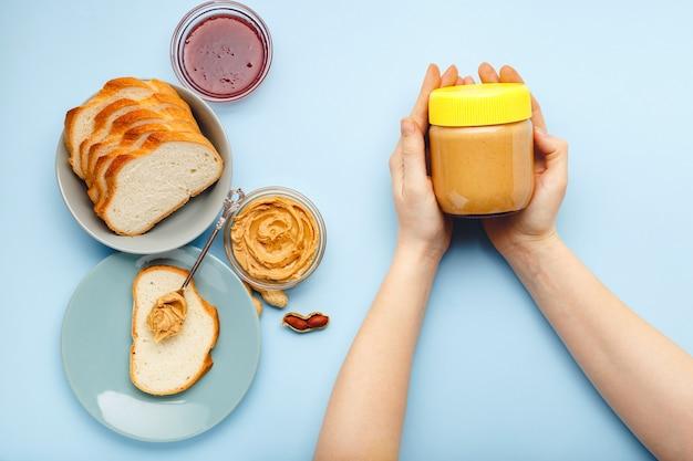 Сливочная арахисовая паста в стеклянной банке с желтой крышкой в женских руках и арахис в кожуре разбросаны по цветному фону.