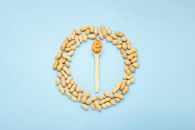 Сливочно-арахисовая паста в деревянной ложке. арахис в кожуре разбросаны кадр на синем фоне