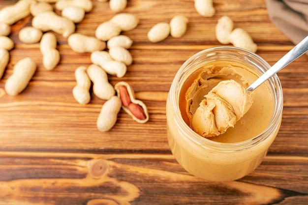 Creamy peanut paste in open glass jar, peanut butter in spoon.