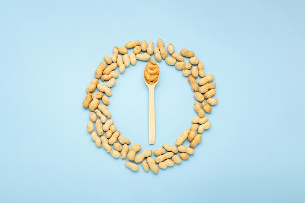 Creamy peanut paste in wooden spoon. peanuts in peel scattered frame on blue background