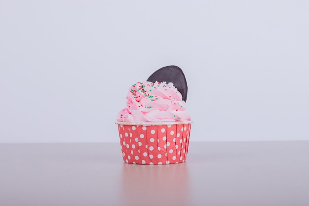 Creamy pink cupcake on white