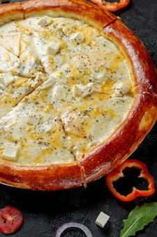 クリーミーなピザとチーズ。暗い背景にオリーブと赤ピーマンを添えた新鮮な自家製イタリアンピザマルゲリータ