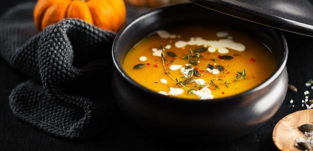Creamy pumpkin soup served in bowl