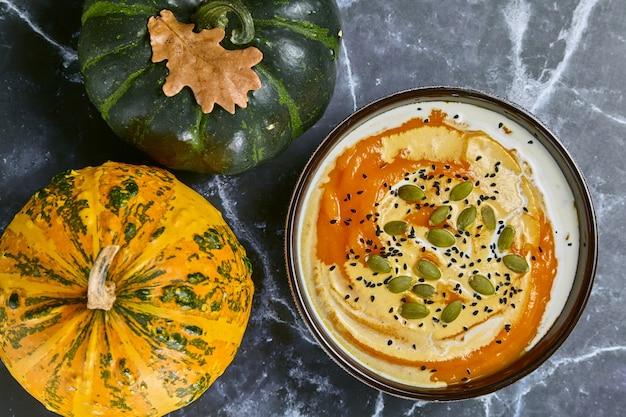 Крем-суп из тыквы со сливками, черным тмином и тыквенными семечками. фото высокого качества