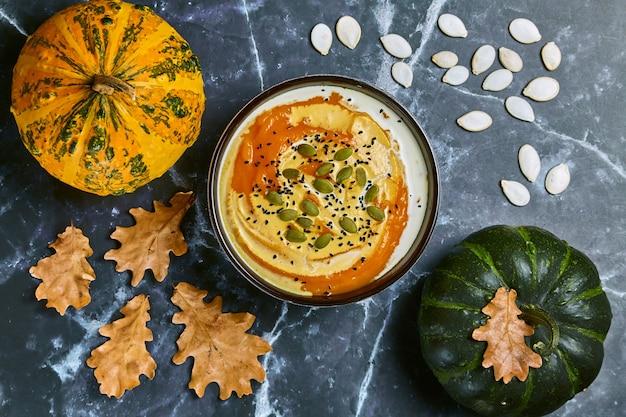 黄色いオークの葉と有機カボチャの暗い大理石のテーブルに対してボウルにクリームと種子のクリーミーなカボチャスープ